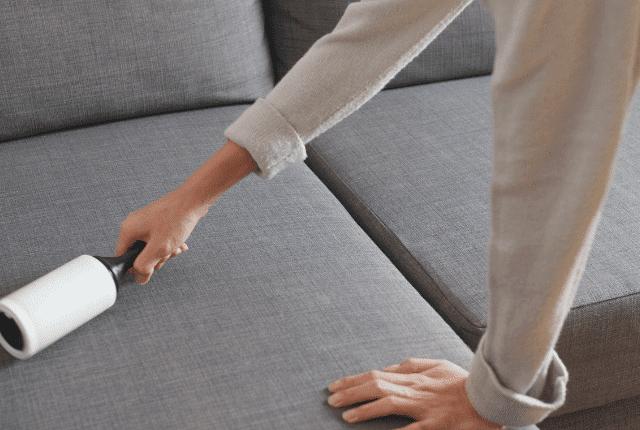 אישה מנקה את הספה