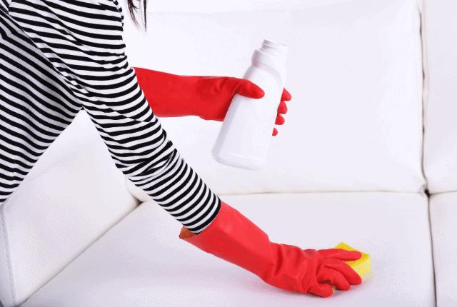אישה מנקה ספה עם חומר