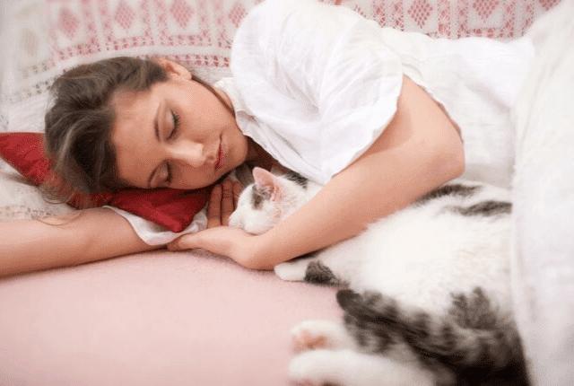 שינה מתוקה ובריאה, אישה וחתולה ישנים במיטה