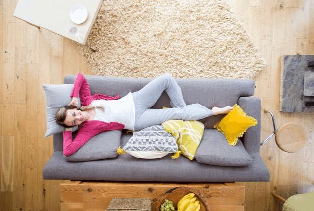 אישה נחה בספה, סלון נקי ויפה
