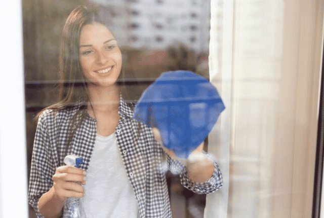 ניקוי עצמאי לחלונות, אישה מבריקה חלון עם מטלית