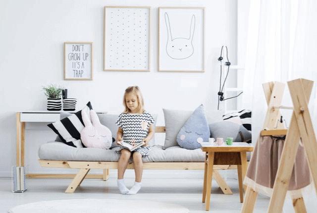 ילדה קוראת ספר בסלון, ספה מעוצבת ונקייה